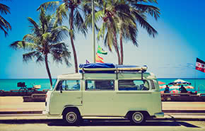 Green old bus on a beach with palms